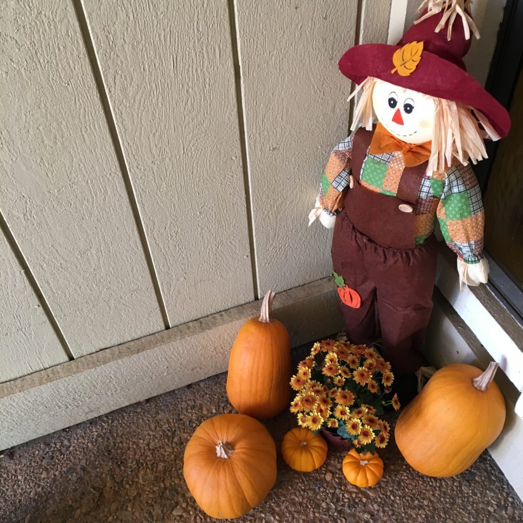 porch scarecrow with pumpkins